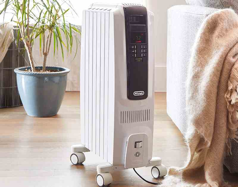 DeLonghi oil-filled space heater beside couch in large room
