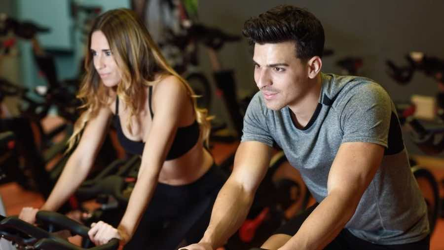 Two people exercising on stationary bikes in a gym