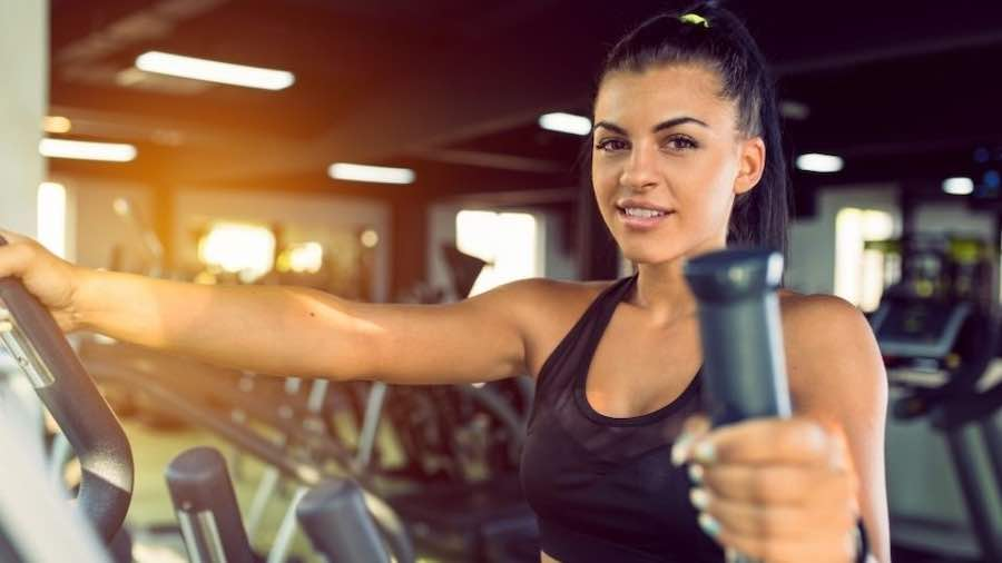 Female focusing on an upper-body workout on an elliptical trainer