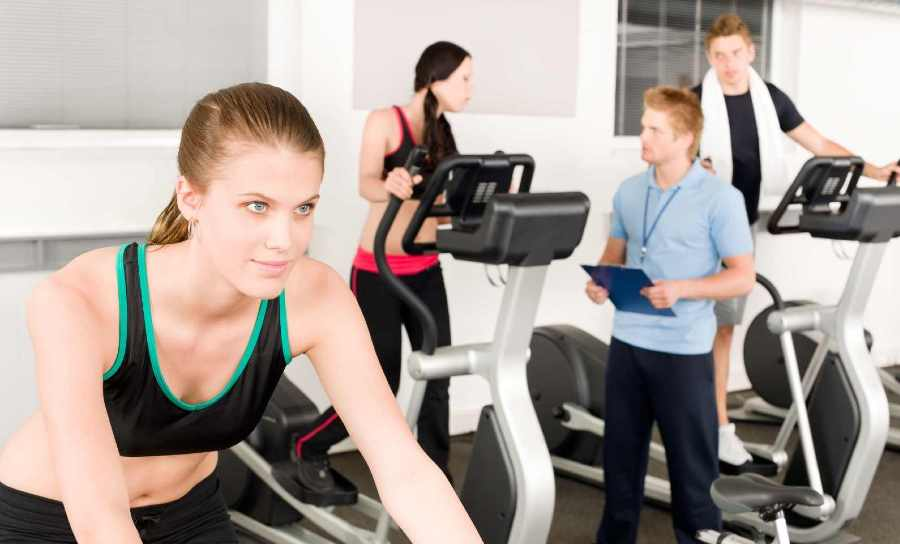 Woman using elliptical beside another woman riding a stationary bike