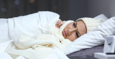Woman bundled in bed considering whether to turn off her space heater
