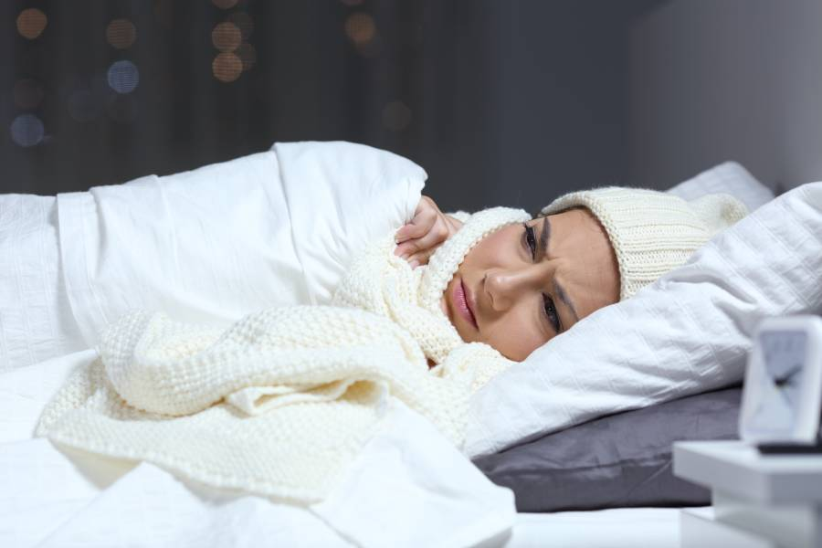Woman bundled in bed contemplating how long she can leave her space heater on