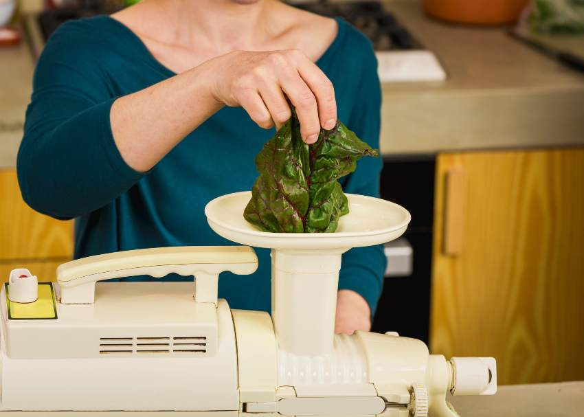 Woman juicing leafy greens using a slow juicer