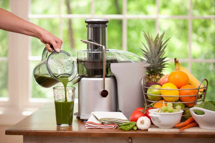 Person pouring fresh juice next to a juicer