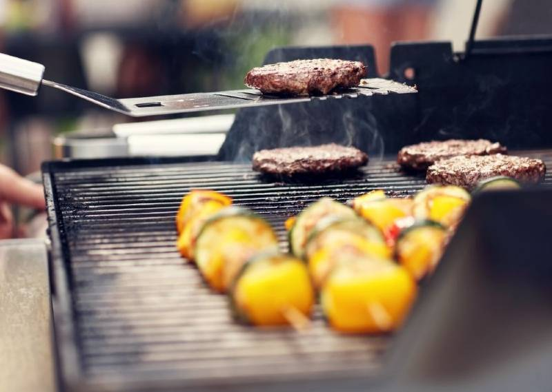 Meat and veggies cooking on a small gas grill