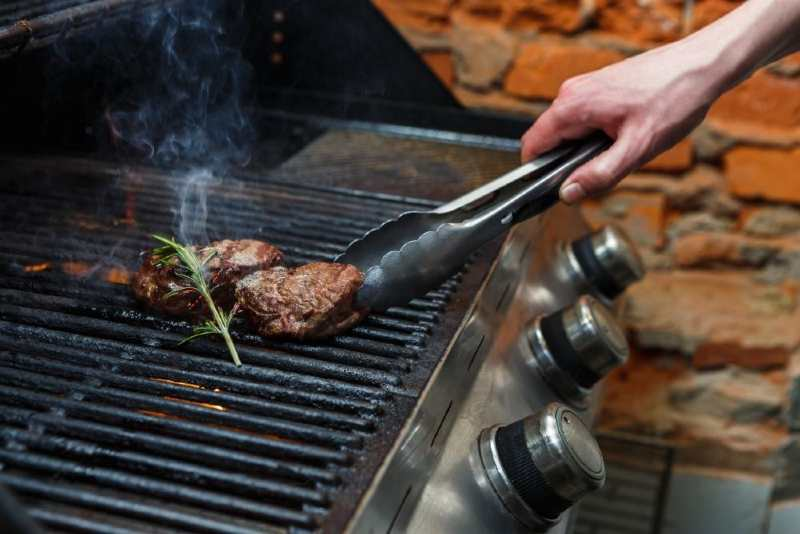 Two pieces of beef cooking on a gas grill