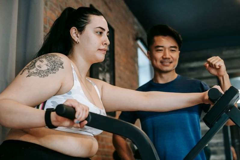 A determined overweight lady doing elliptical training with a personal trainer