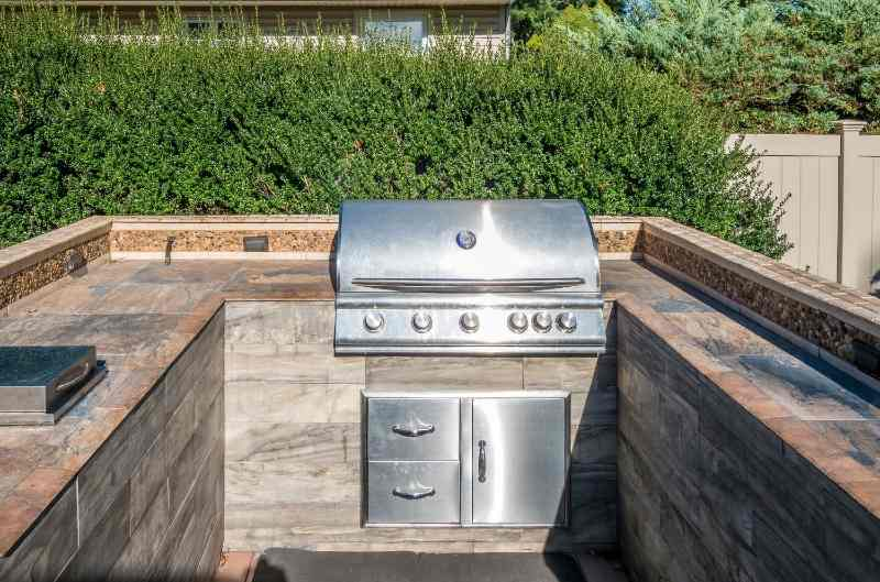 Built-in grill as a part of an open-roof backyard kitchen