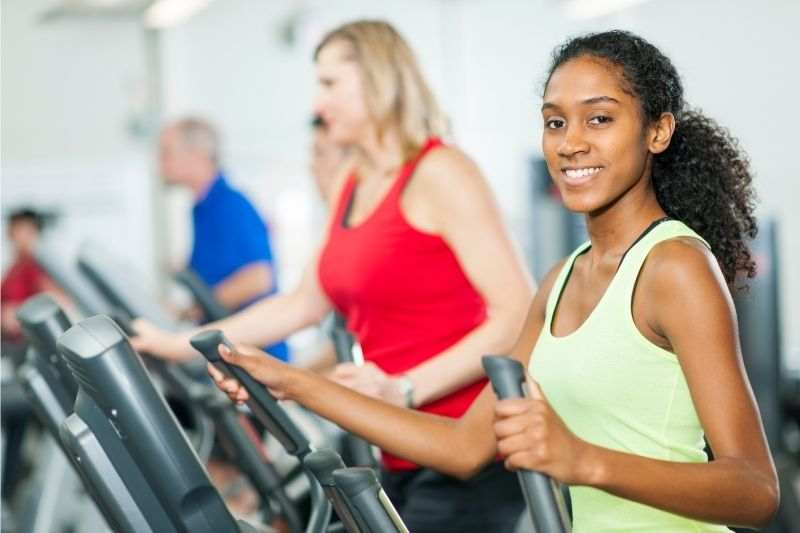 A young woman exercising on an elliptical cross trainer