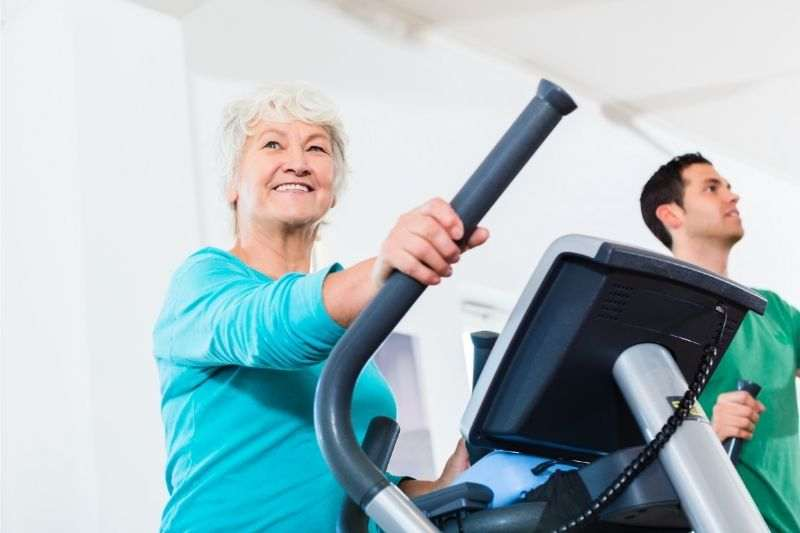 A senior lady doing cardio on an elliptical cross trainer