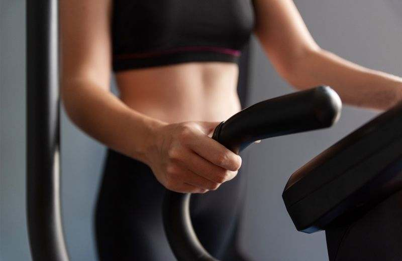 A close-up of a woman's hands holding the elliptical handles