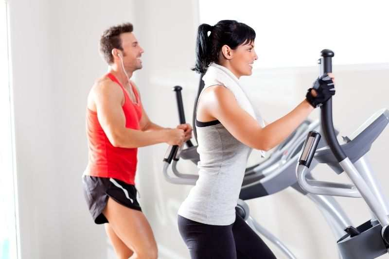 A couple of sports enthusiasts doing cardio on elliptical machines