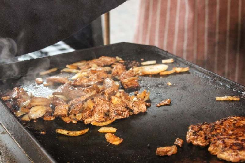 Grilled meat and veggies on a griddle surface