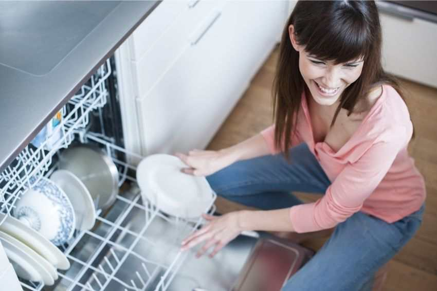 A woman clearing out the dishwasher