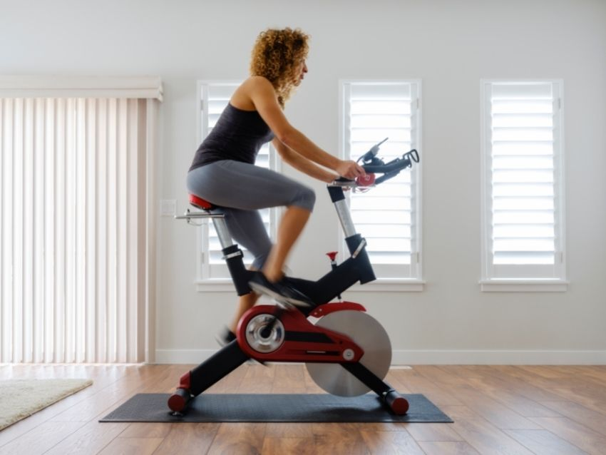 A woman exercising on a magnetic spin bike at home.