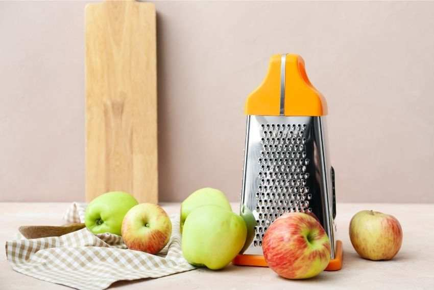 A standard grater and some apples on the kitchen counter
