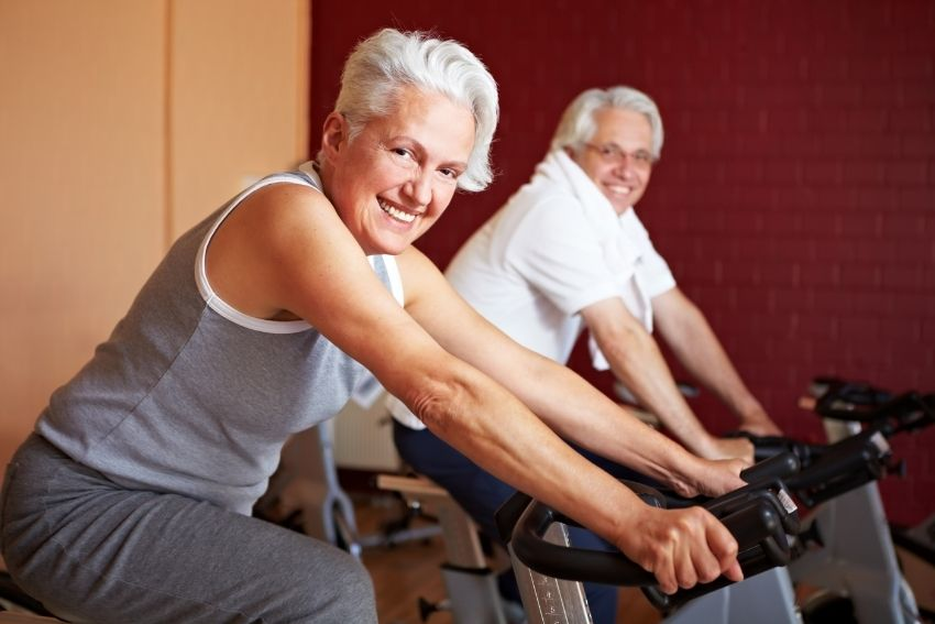 A senior couple exercising on spin bikes at home