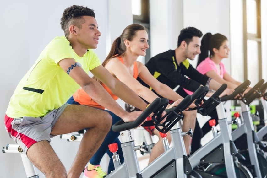 A group of four young people cycling together on spin bikes