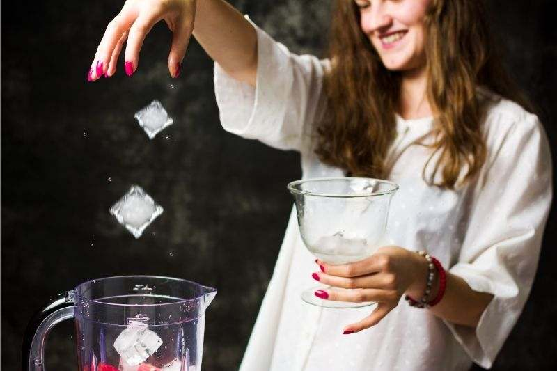 A young girl making frozen drinks with a blender