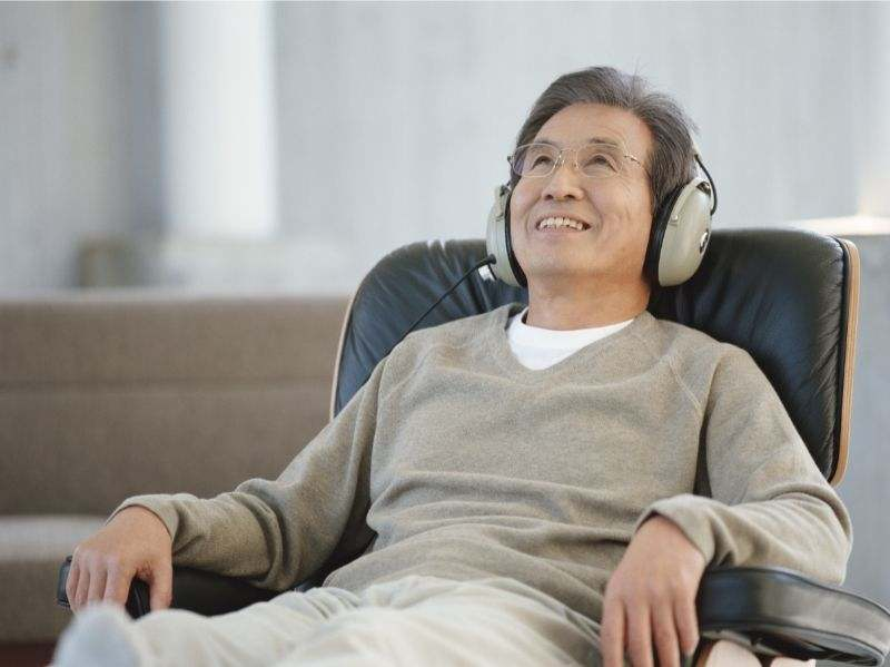 A senior man relaxing in a recliner, listening to music