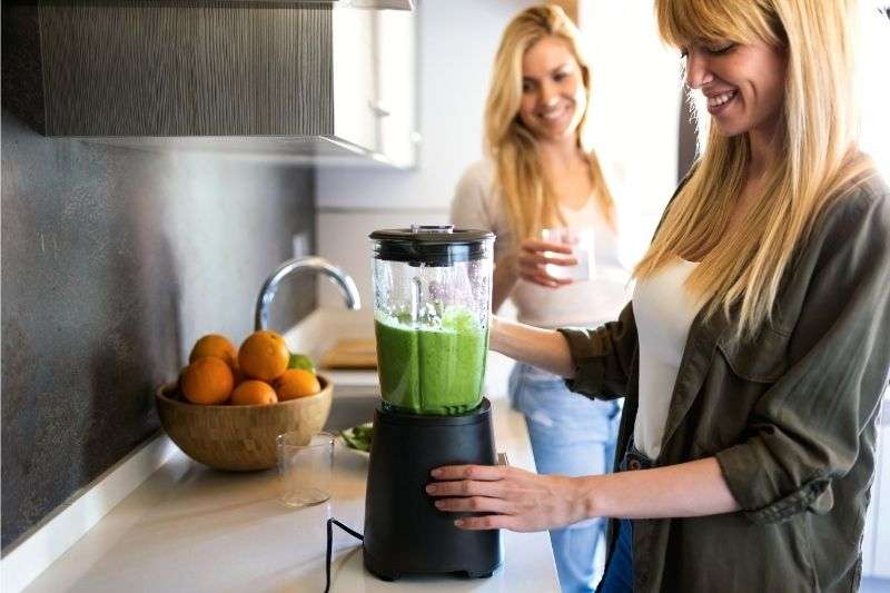 A couple of young women making green juice