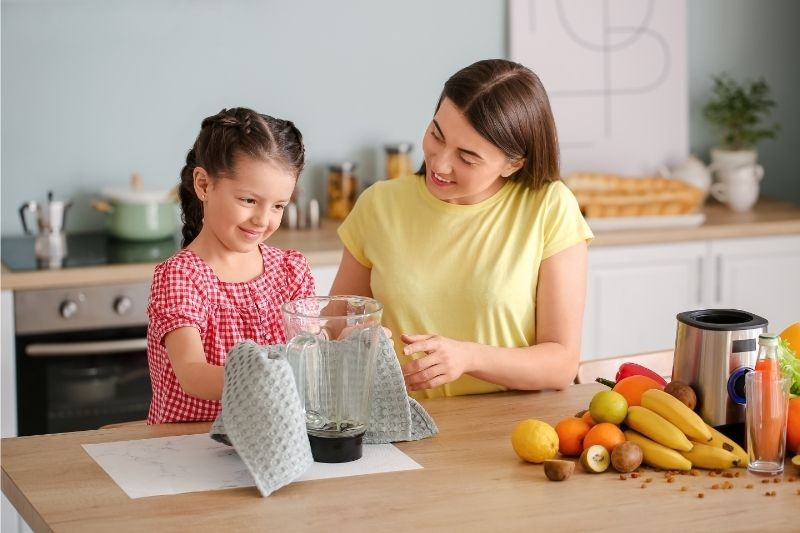 A woman and a girl finishing up the blender cleaning process