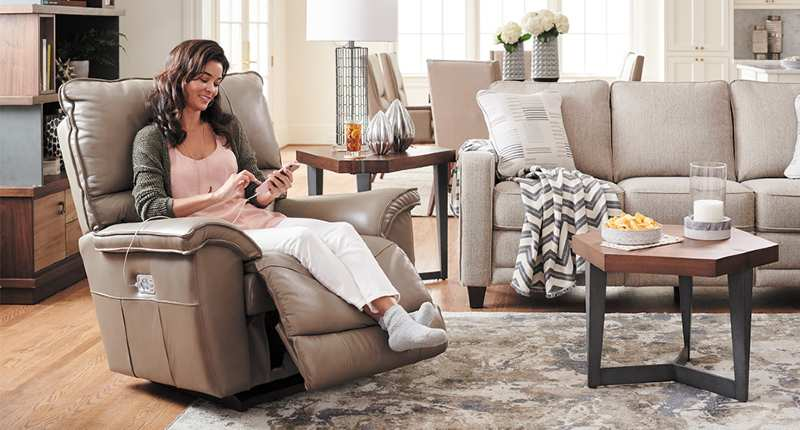 A woman charging her phone through a recliner