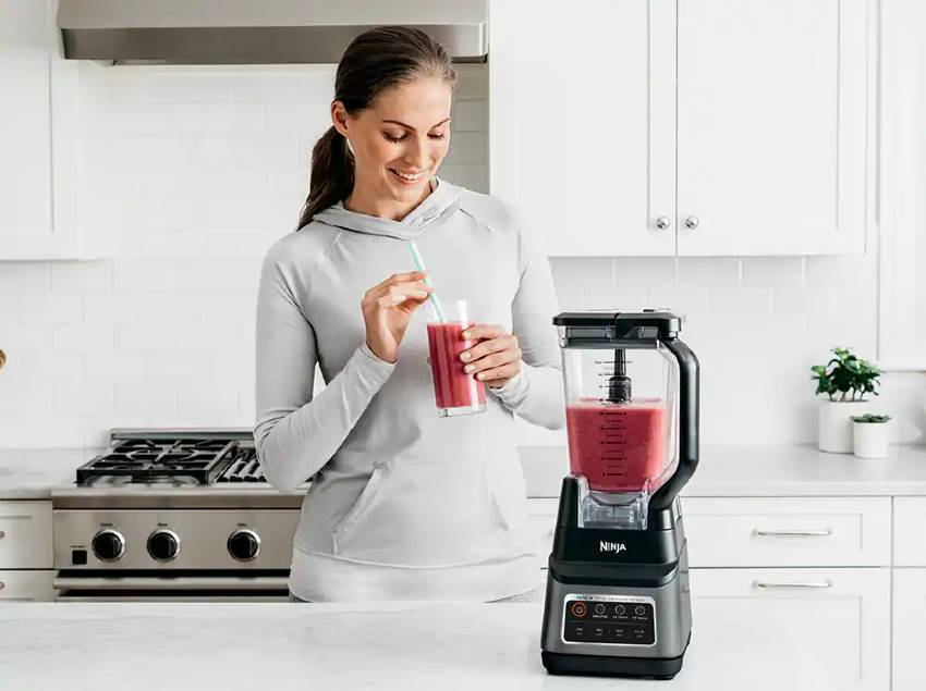 A woman using a Ninja blender to make a red smoothie