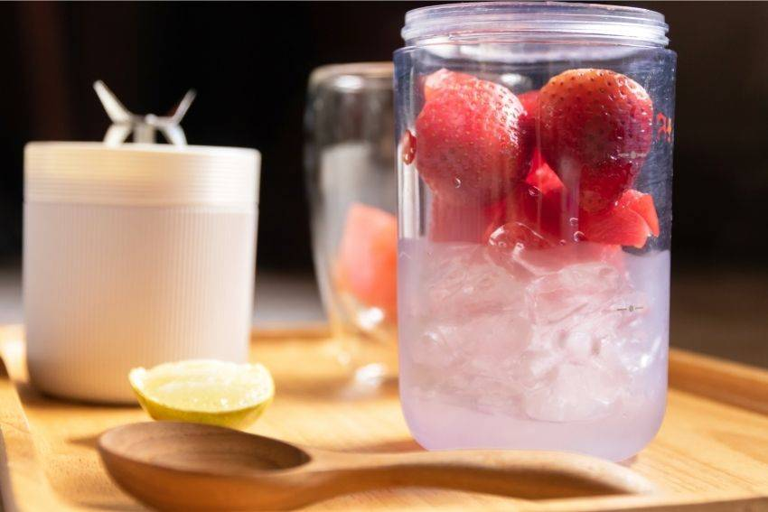A portable blender container full of strawberries and ice