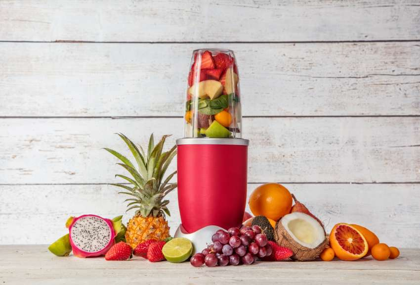 A slim blender surrounded with all sorts of colorful fruits