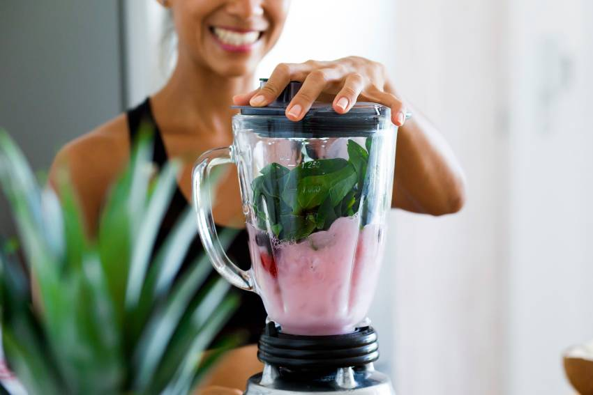 A woman making a green and pink smoothie with a blender
