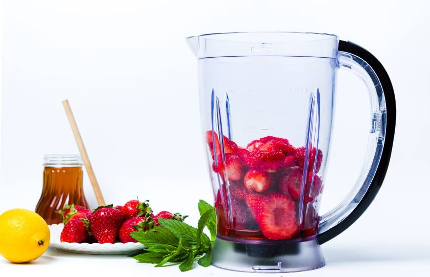 A large blender pitcher full of strawberries