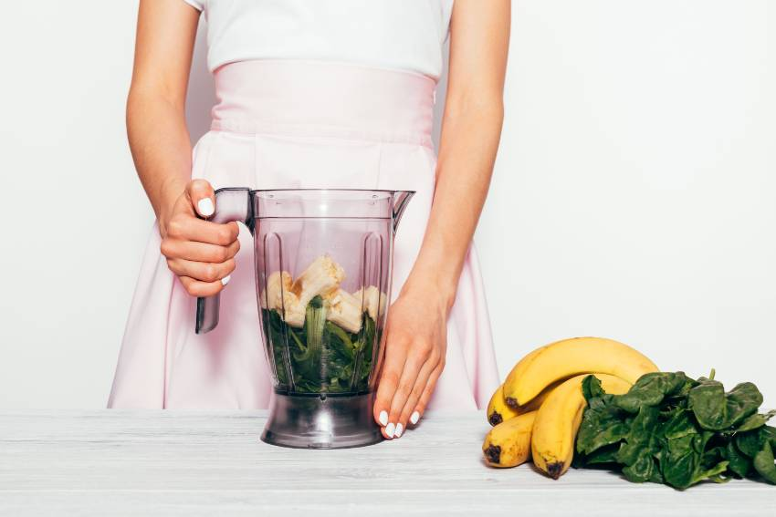 A woman getting ready to blend a green banana smoothie