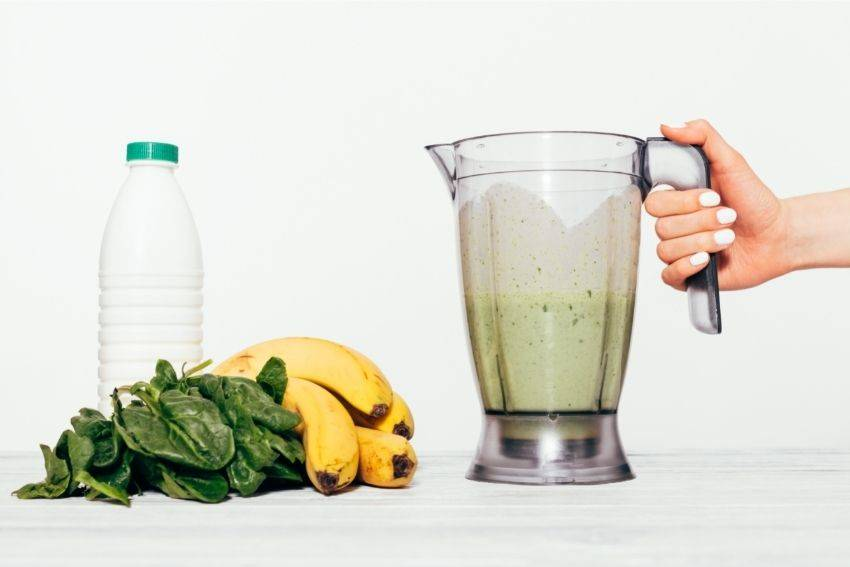 A full blender pitcher next to greens and bananas