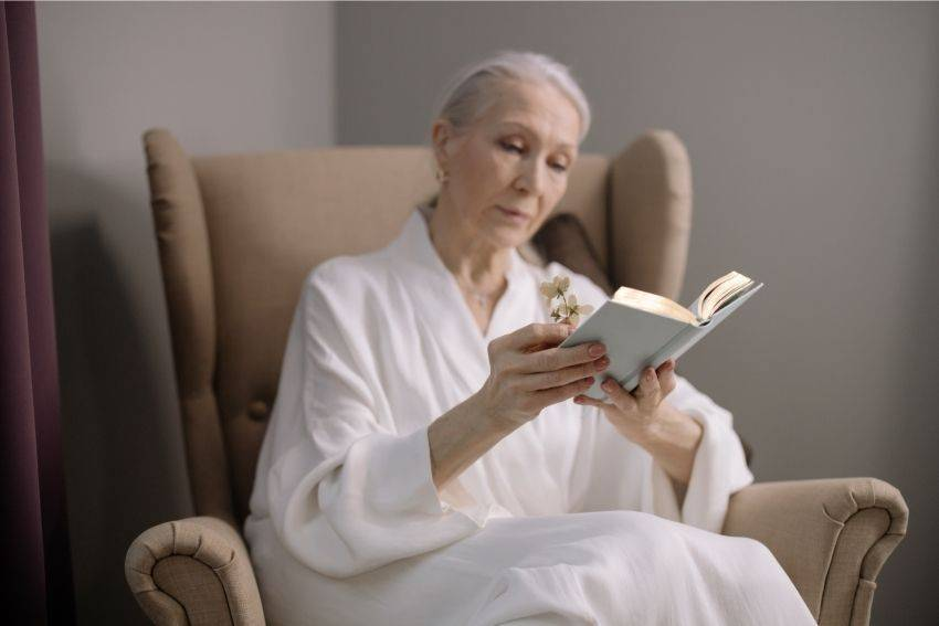 Elderly lady sitting in a recliner, reading a book