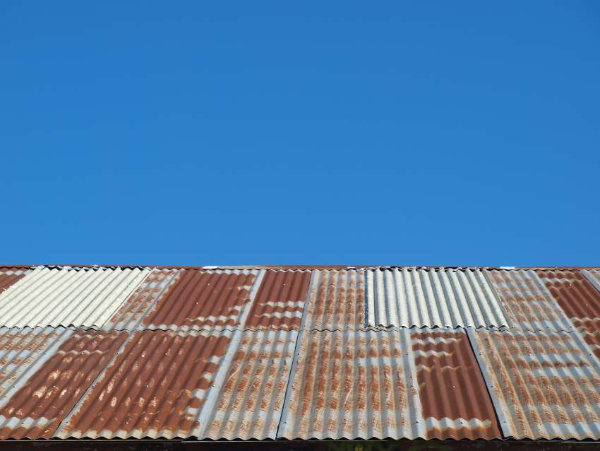 Rusty metal roofing against a bright blue sky