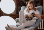 Young woman reading a book in a recliner chair