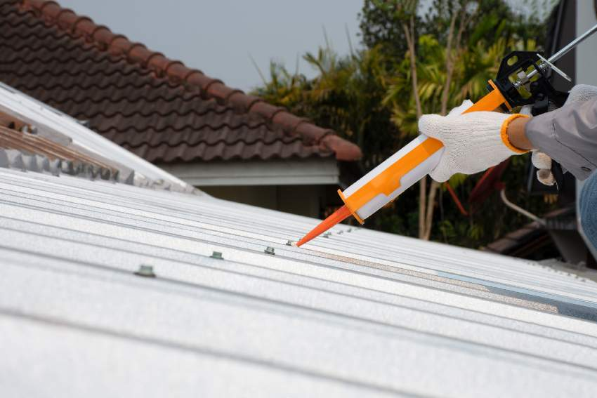 Hands applying metal roofing sealant from a cartridge