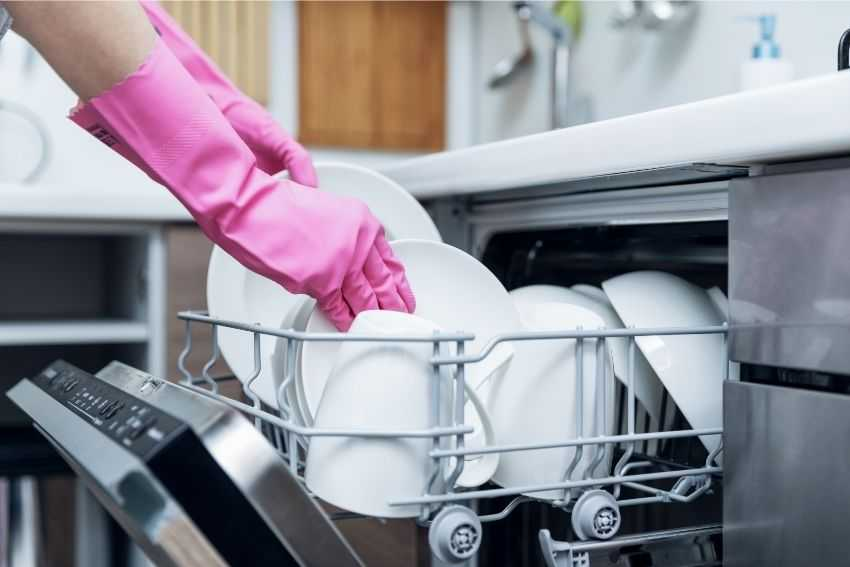 A person working on unloading the dishwasher