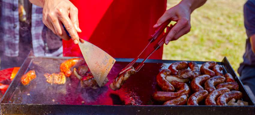 A griddle cheff cooking meat on a griddle