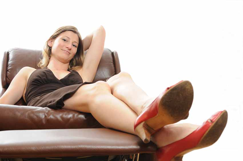 Woman slouching on a swivel recliner with her feet hanging over the footrest