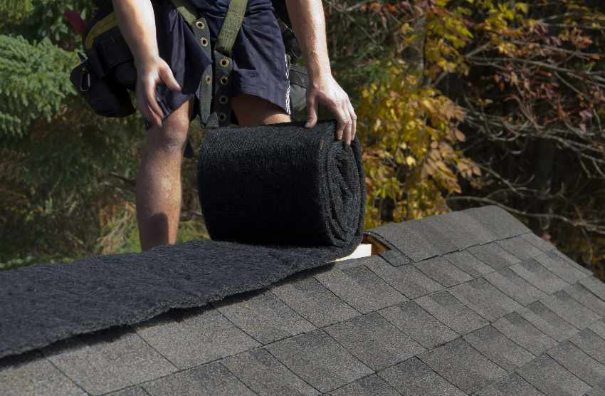 A person installing ridge vent in a roll onto a roof