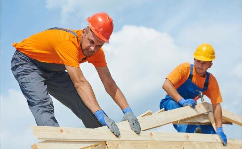 Two construction workers working on a new roof