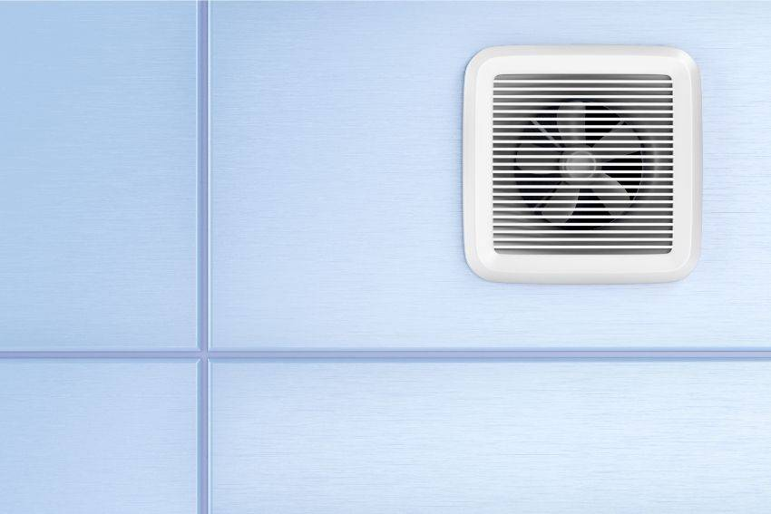 A clean new bathroom exhaust fan on a tile wall