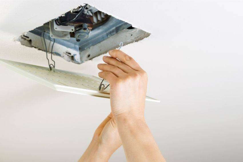 A pair of hands changing the bathroom exhaust fan