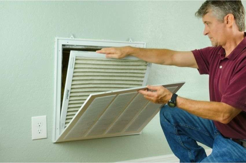 A man replacing his old AC filter in the house