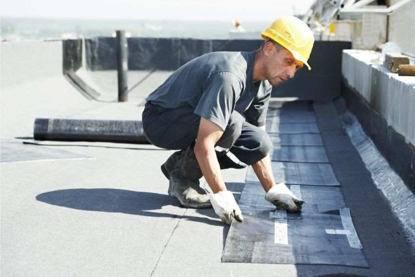 A construction worker laying down protective layers on the roof