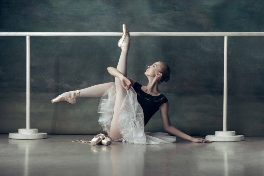 A ballerina posing in front of a ballet barre