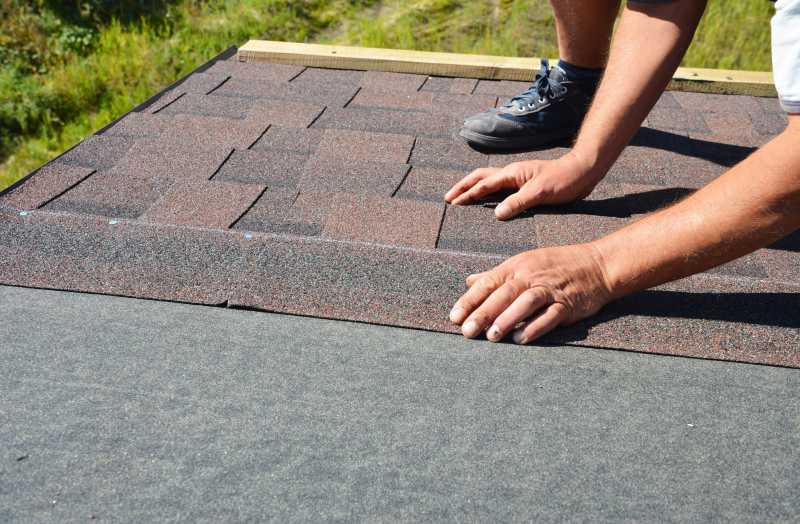 A worker lays new shingles on the protective roof underlayment
